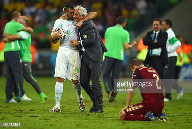 Essaid Belkalem of Algeria celebrates with head coach Vahid Halilhodzic as a dejected Aleksei Kozlov of Russia looks on during the 2014 FIFA World...
