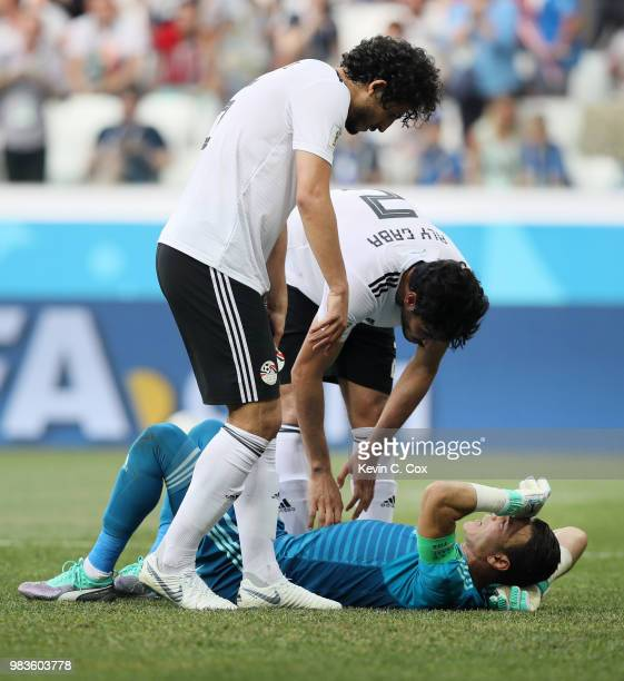Essam El Hadary of Egypt lies on the pitch injured as Ali Gabr and Ahmed Hegazy check on his condition during the 2018 FIFA World Cup Russia group A...