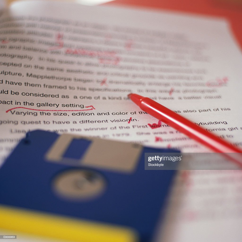 Essay paper with floppy diskettes lying on top, red pen beside them : Stock Photo
