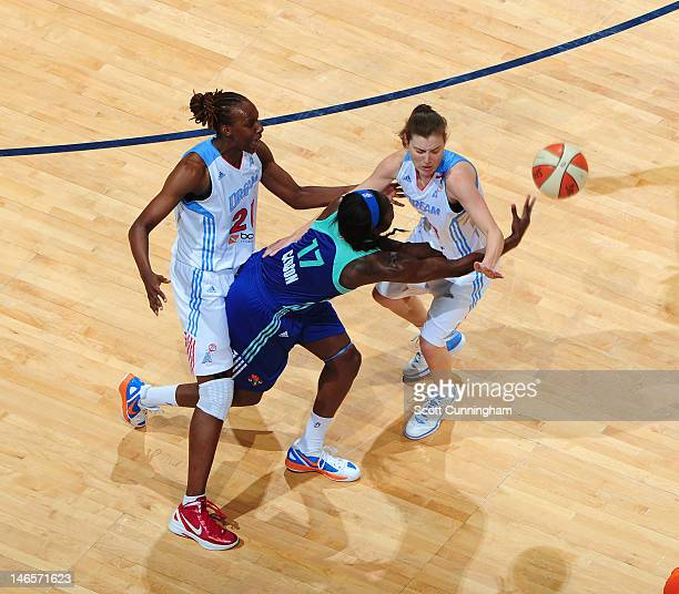 Essence Cardon of the New York Liberty passes the ball around the defense of Laurie Koehn and Sancho Lyttle of the Atlanta Dream at Philips Arena on...
