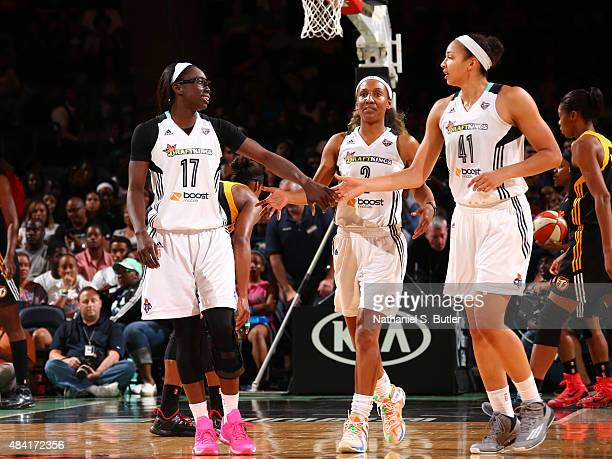 Essence Carson hi fives Kiah Stokes and Candice Wiggins of the New York Liberty on August 15 2015 at Madison Square Garden New York City New York...