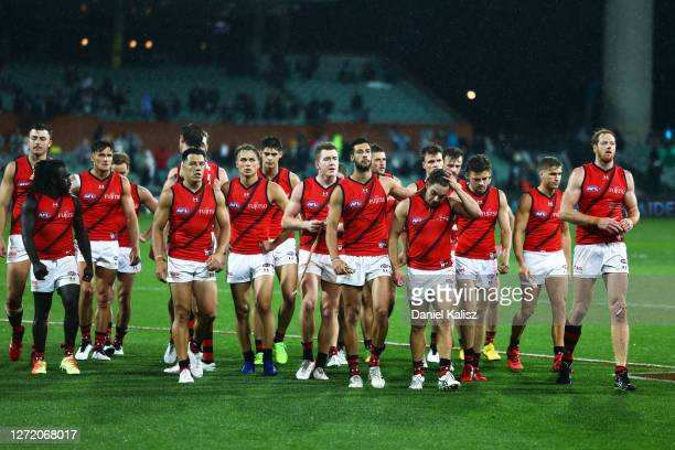 Essendon Bombers players walk from the ground looking dejected during the round 17 AFL match between the Port Adelaide Power and the Essendon Bombers...