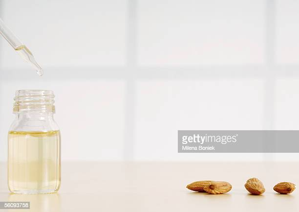 Essential oil, dropper and almonds
