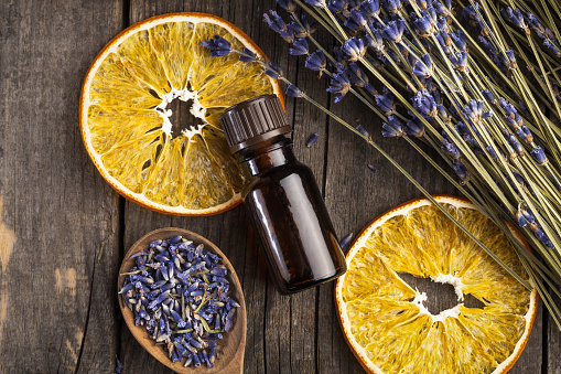 Essential oil lavender and orange dry on a wooden table, top view 1134054641