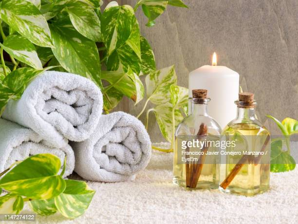 essential oils and towels on table - aromatherapy stock pictures, royalty-free photos & images