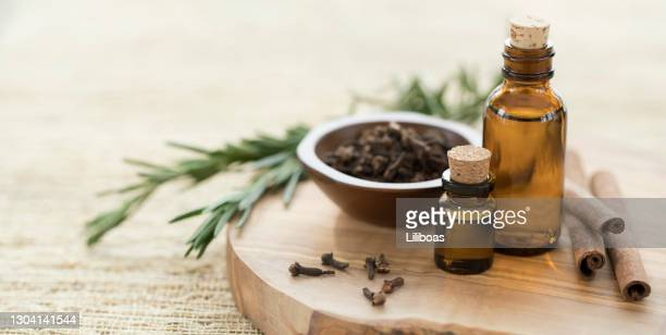 essential oils with rosemary, cloves & cinnamon. - aromatherapy oil stock pictures, royalty-free photos & images