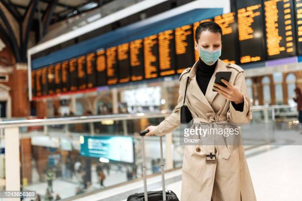 essential travels during lockdown - woman with face mask checking in online while waiting near arrival departure board - coronavirus stock pictures, royalty-free photos & images
