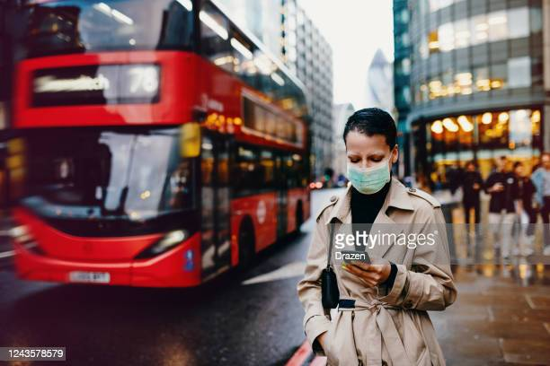 essential worker in london with face mask going back home after work with face mask on - high street stock pictures, royalty-free photos & images