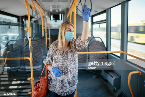 essential worker with face mask and gloves commuting by bus - frontline worker stock pictures, royalty-free photos & images