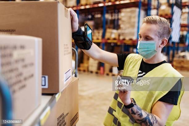 essentiële werknemers in de dienst- en bezorgindustrie met gezichtsmasker tijdens covid-19 pandemie - vrachtvervoer stockfoto's en -beelden