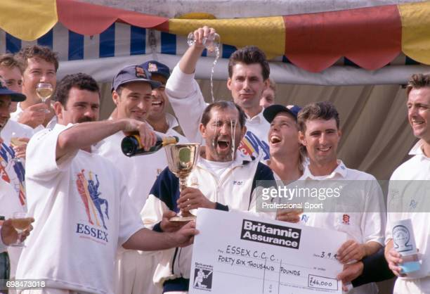 Essex captain Graham Gooch gets a champagne shampoo from Neil Foster as Essex celebrate winning the Britannic Assurance County Championship after...