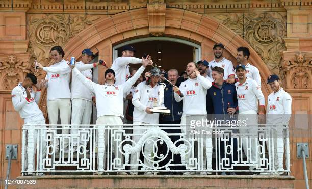 Essex captain Tom Westley holds the Bob Willis Trophy as he celebrates on the Pavilion balcony with his teammates and head coach Anthony McGrath...