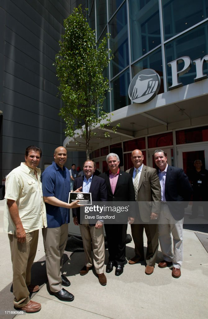 Essex County Executive Joseph DiVincenzo Jr., Newark mayor Cory Booker, NHL commissioner Gary Bettman, chairman and managing partner of the New Jersey Devils Jeff Vanderbeek, former hockey player and three-time Stanley Cup champion Ken Daneyko and New Jersey Devils radio announcer Matt Loughlin pose with a plaque after the New Jersey Legacy Tree Project Press Conference at Prudential Center on June 29, 2013 in Newark, New Jersey. As part of the NHL's commitment to support the local environment of host cities for NHL events through its NHL Green initiative, the NHL Foundation has donated 30 trees to the Devils Care Foundation.