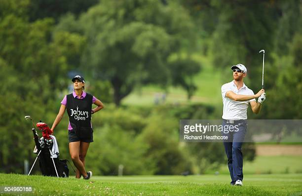 Estanislao Goya of Argentina is watched by caddie and Ladies European Tour player Henrietta Zuel on the East Course during day one of the Joburg Open...
