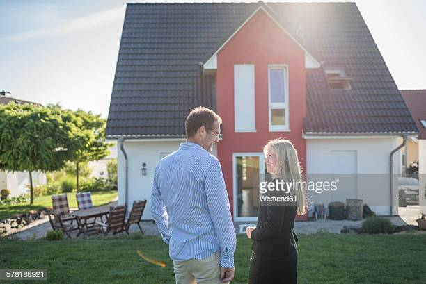 Estate agent and customer standing in front of one-family house