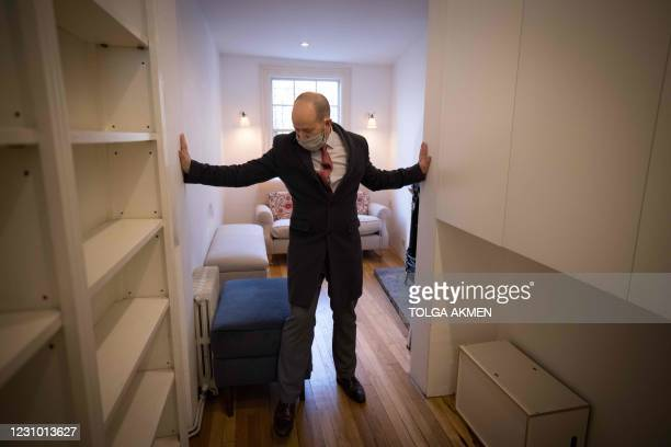 Estate agent David Myers leads a tour of what is dubbed 'London's thinnest house' in west London on February 5, 2021. - Wedged neatly between a...