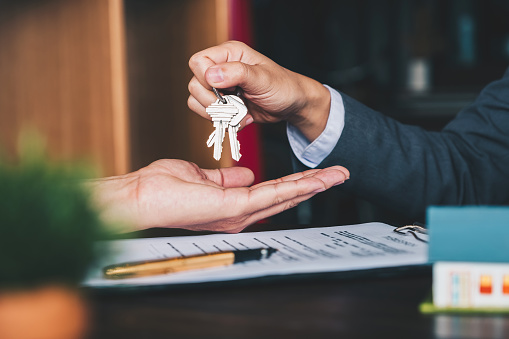 estate agent giving house keys to woman and sign agreement in office 1130829500