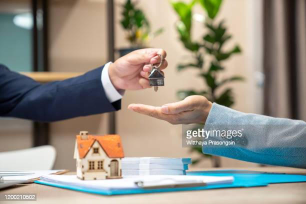 estate agent giving house keys to woman and sign agreement in office - mortgage loan stock pictures, royalty-free photos & images