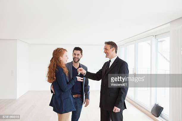 Estate agent handing over keys to young couple