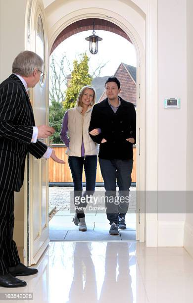 Estate agent inviting young couple into new house