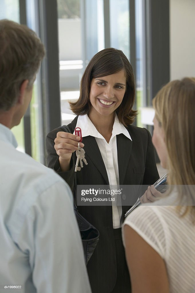 Estate Agent Offering Keys to a Couple in an Apartment : Stock Photo
