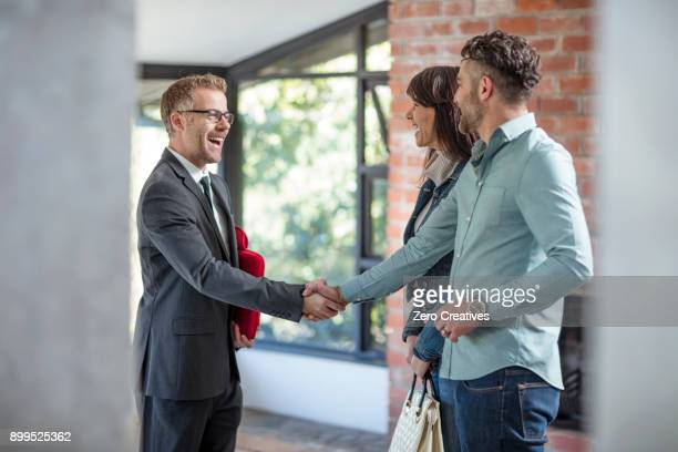 estate agent shaking hands with couple in empty home - selling stock pictures, royalty-free photos & images