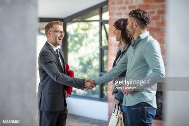 estate agent shaking hands with couple in empty home - agente inmobiliario fotografías e imágenes de stock