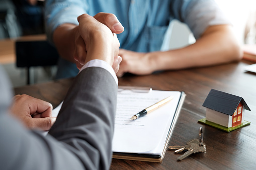 Estate agent shaking hands with his customer after contract signature 1127717245