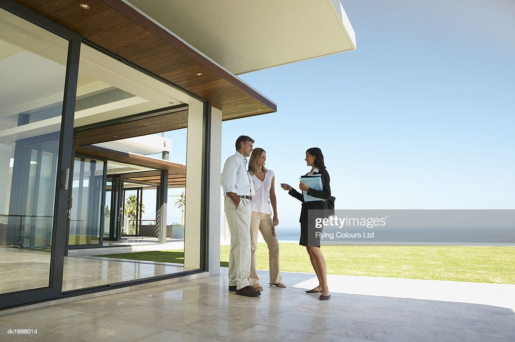 Estate Agent Showing a Couple a House : Stock Photo