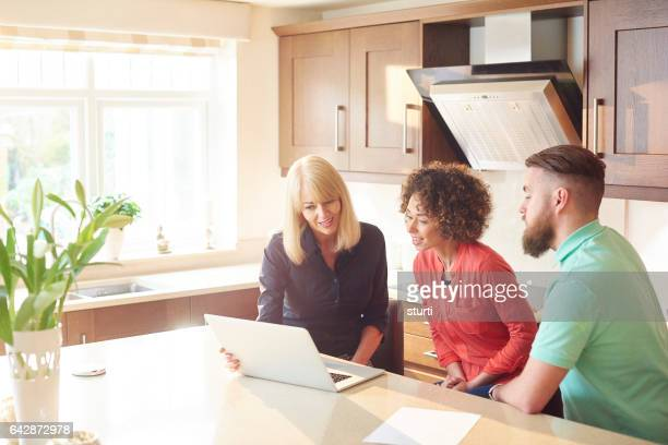 estate agent with couple looking at figures