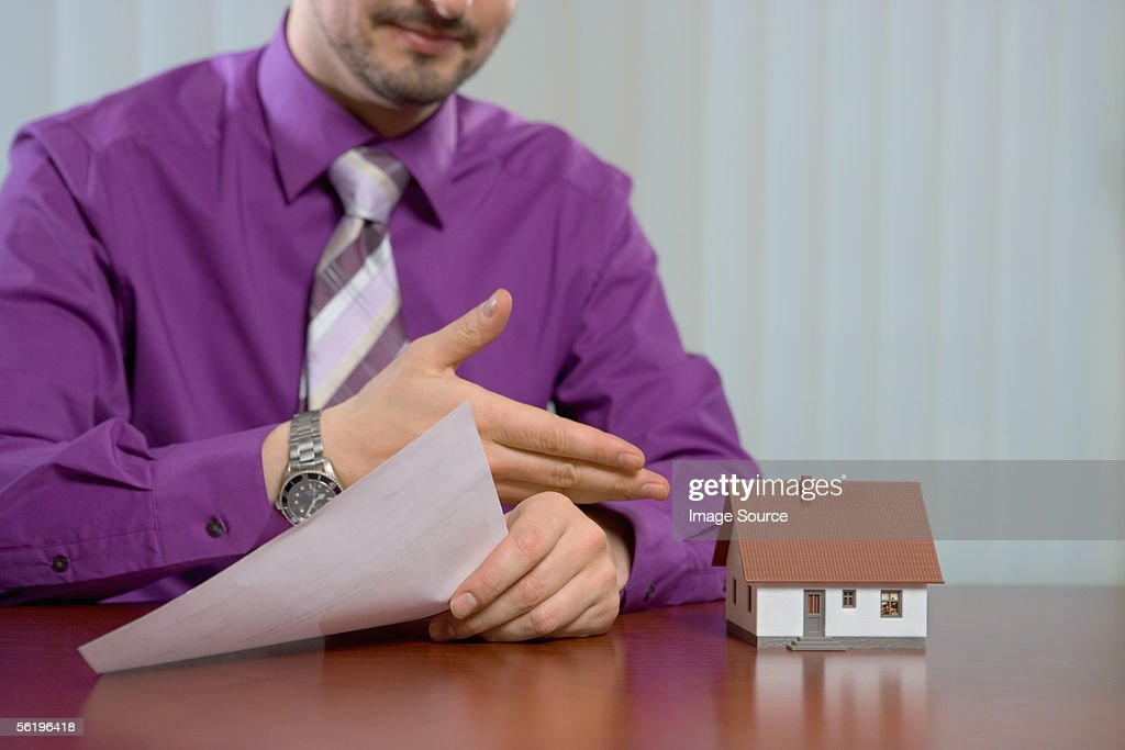 Estate agent with model house : Stock Photo