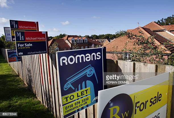 Estate Agents advertising boards boards are pictured outside a small housing estate on the outskirts of Reading in south-west England, on October 1,...