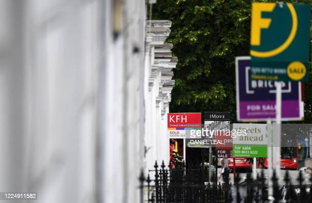 """Estate Agents' """"For Sale"""", """"Sold"""", and """" To-Let"""" boards are pictured outside residential properties in south London on July 6, 2020. - British media..."""