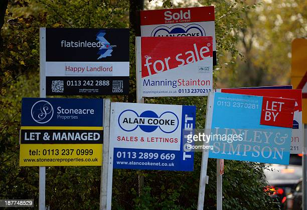Estate agents for sale to let and let by boards stand near residential buildings in Leeds UK on Tuesday Nov 12 2013 Under Bank of England Governor...