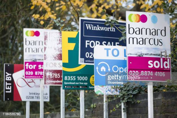Estate agents' property for sale boards sit attached to a wall outside a block of flats in the Putney district of south-west London, U.K., on Monday,...
