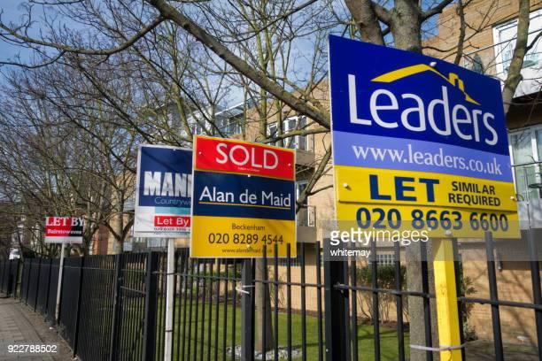 Immobilienmakler Zeichen außerhalb eines Mehrfamilienhauses