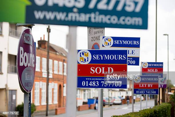 Estate agents' 'Sold' 'Let By' and 'For Sale' signs sit in front of a residential property in Woking Surrey UK on Monday Sept 14 2015 In a recent...