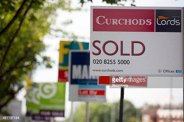 Estate agents' 'Sold' 'Let By' and 'For Sale' signs stand outside a residential apartment block located in the Kingston area of London UK on Monday...