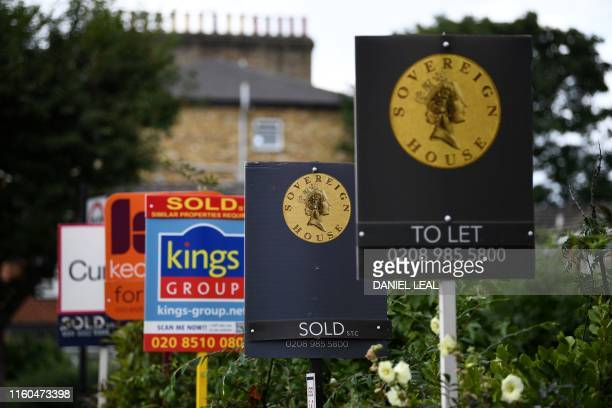 Estate and rental agents' boards are pictured on a residential street in Hackney east London on August 9 2019 House prices and sales are losing...