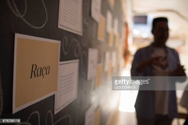 Esteban Cipriano in charge of education programs at the antiracism group ID_BR talks to employees of fashion brand Maria Filo next to a sign reading...