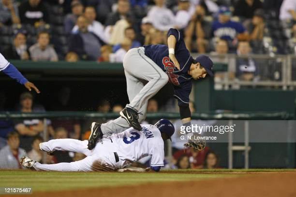 Esteban German of the Royals slides into 3rd base ahead of the throw as Cleveland's Aaron Boone flies over him during action between the Cleveland...