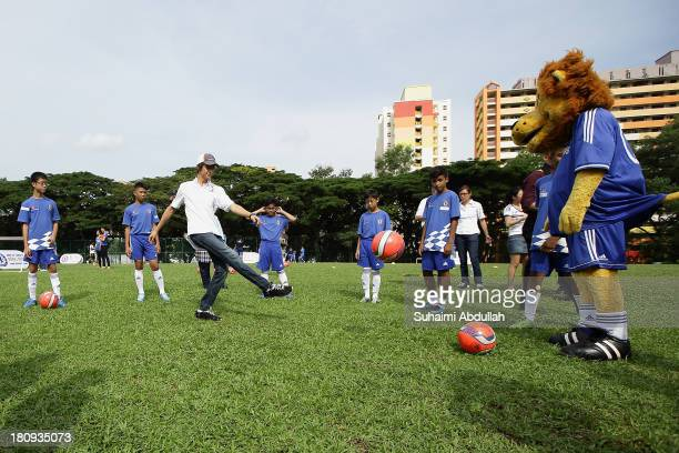 Esteban Gutierrez of Mexico and Sauber F1 team joins local youth from the Chelsea FC Soccer School Singapore in a football clinic kickabout during...