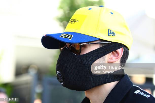 Esteban Ocon of France and Renault Sport F1 walks through the Paddock wearing a mask during previews ahead of the F1 Grand Prix of Australia at...