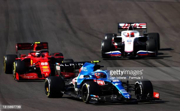Esteban Ocon of France driving the Alpine A521 Renault leads Carlos Sainz of Spain driving the Scuderia Ferrari SF21 and Nikita Mazepin of Russia...