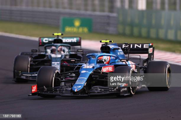 Esteban Ocon of France driving the Alpine A521 Renault leads Sebastian Vettel of Germany driving the Aston Martin AMR21 Mercedes during the F1 Grand...