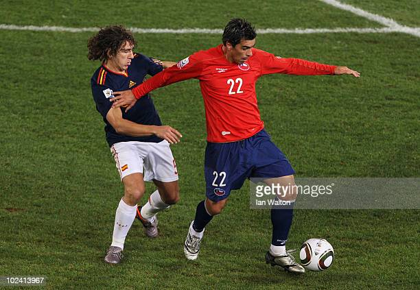 Esteban Paredes of Chile fends off the challenge of Carles Puyol of Spain during the 2010 FIFA World Cup South Africa Group H match between Chile and...