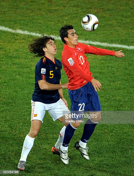 Esteban Paredes of Chile wins the ball ahead of Carles Puyol of Spain during the 2010 FIFA World Cup South Africa Group H match between Chile and...