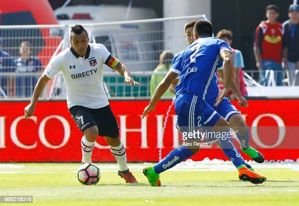 Esteban Paredes of Colo Colo fights for the ball with Christian Vilches of U de Chile during a match between U de Chile and Colo Colo as part of...