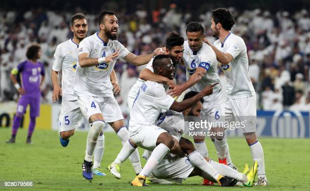 Esteghlal FC's players celebrate after scoring a goal against AlAin FC during their AFC Champions League group match at Hazza Bin Zayed Stadium on...