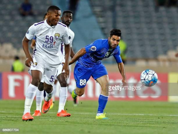 Esteghlal's Farshid Esmaieli kicks the ball past alAin's Saeed Juma during the 2017 AFC Champions League round 16 football match between Iran's...